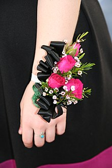 A Modern Wrist Corsage Made With Black Satin Ribbon Pink Spray Roses And Wax Flower