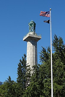 The column of the Prison Ship Martyrs' Monument, topped by a bronze urn, among trees, with a modern American and POW/MIA flagstaff adjoining.