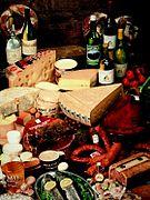 photographie représentant divers spécialités culinaire franc-comtoises dont les saucisses de Morteau et Montbéliard, des fromages tels le comté, la cancoillotte, le mont d'or et des vins du Jura