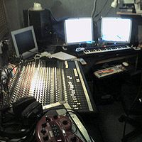 "A control room with a mixing console, monitor speakers, and computer-based ""DAW""."