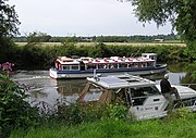 Leisure activities on the River Avon at Avon Valley Country Park, Keynsham, Bristol, England. A boat giving trips to the public passes a moored private boat.