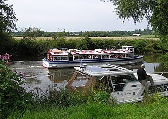 Leisure activities on the River Avon at Avon Valley Country Park, Keynsham, United Kingdom. A boat giving trips to the public passes a moored private boat. River avon at keynsham arp.jpg