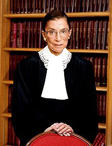 Ginsburg standing in front of a bookshelf