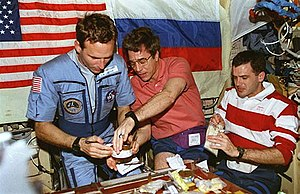 STS-81 - Mission Specialists Jerry Linenger, John Blaha and Jeff Wisoff gather around the wardroom table, sampling Russian food.