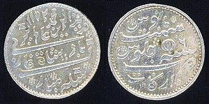 Obverse and reverse - Silver rupee using Mughal conventions, but minted by the British East India Company Madras Presidency between 1817 and 1835. On rupees, the side that carries the name of the ruler is considered the obverse.