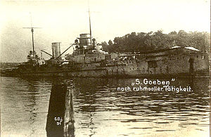 A black and white image of a warship that has become beached. It is listing to starboard. A caption is written in white ink in German over the top of the image.
