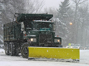 A green truck pushing a yellow snowplow amid falling snow.