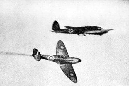 British Supermarine Spitfire fighter aircraft (bottom) flying past a German Heinkel He 111 bomber aircraft (top) during the Battle of Britain (1940) Spitfire and He 111 during Battle of Britain 1940.jpg