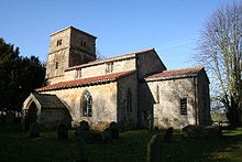 A stone church with a red tiled roof seen from the southeast, with a small chancel, a larger nave with clerestory and porch, and a tower