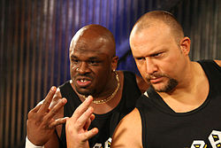 Two adult males, one black and one white, wearing black shirts doing hand gestures.