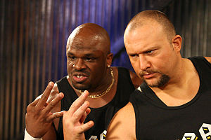 The Dudley Boyz - D-Von and Bubba Ray making the 3D taunt (index finger and thumb forming the lower part of a 'd', the middle finger forming the upper part of the 'd' while also representing the number 3 along with the two remaining digits).