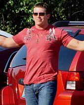 A dark haired young man wearing dark sunglasses poses for cameras with his arms outstretched. He is wearing a red T-shirt, with a pattern on both shoulders and the top part of the chest, and jeans.