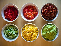 small bowls of corn, tomatoes, peppers, guacamole, and other ingredients