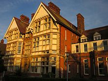 Two 3-story gabled towers of Thanet College, in late sun.