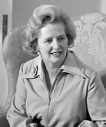 Margaret Thatcher in a jacket with a brooch on a lapel, sitting in an armchair.