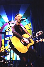 O'Riordan onstage with a large acoustic guitar