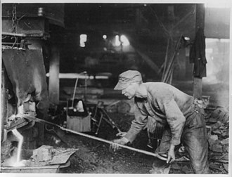 """Steel strike of 1919 - View of a steelworker at his work of puddling, where he is """"working up"""" his """"ball of iron"""". (1919)"""