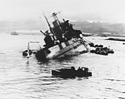 A large warship rolls over on its side