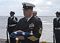 US Navy 070117-N-9805F-004 Command Master Chief Christopher Engles renders honors by receiving the ensign for the family of the deceased during a burial at sea aboard USS Theodore Roosevelt (CVN 71).jpg
