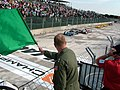US Navy 070421-N-7665S-074 Commander, Naval Strike and Air Warfare Center, Rear Adm. Mark T. Emerson, waves the green flag to signal the start of the American Le Mans Series sport car race at Houston.jpg
