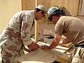 US Navy 080502-N-5709C-004 Builder 3rd Class Christopher Ross, a Seabee assigned to Naval Mobile Construction Battalion (NMCB) 3, and an Iraqi soldier helps measure and cut a piece of plywood sheeting.jpg