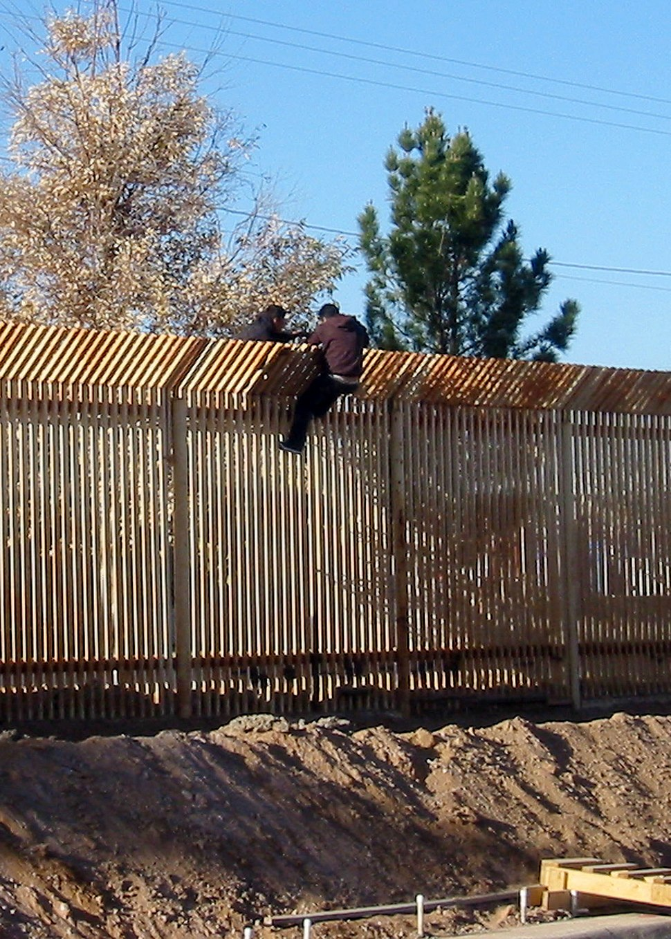 US Navy 090317-N-5253T-016 Two men scale the border fence into Mexico a few hundred yards away from where Seabees from Naval Mobile Construction Battalions (NMCB) 133 and NMCB-14 are building a 1,500 foot-long concrete-lined dr