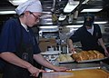 US Navy 091104-N-6692A-085 Culinary Specialist Seaman Levi Chute, left, cuts cornbread into portions while Culinary Specialist Seaman Shawn Carlile prepares loaves of bread for dinner aboard the amphibious dock landing ship USS.jpg
