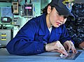 US Navy 100310-N-4774B-112 Quartermaster Seaman Apprentice Kimberly Ramirez, from Las Vegas, uses a slide rule to calculate chart measurements on the bridge of the guided-missile cruiser USS Bunker Hill (CG 52).jpg
