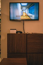 "A television screen placed above a placard with a controller next to it. The television is displaying part of the ""Confusion Ending"" of the remake, in which the player is told to follow a painted yellow line through the office."