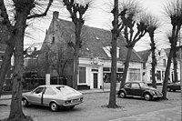 Voorgevel van winkel-woonpand, leibomen en geparkeerde auto's op de voorgrond - Etten-Leur - 20398503 - RCE.jpg