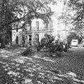 Voorgevel van wit pand, gezien tussen de bomen en deels in de steigers - Baarn - 20401960 - RCE.jpg