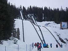 Two snow-covered ski jumps, surrounded by evergreen trees.