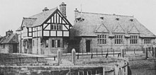 An old photograph showing, from a slight angle, a house on the left and a school on the right.  The house is in stone with a jettied timber-framed upper storey; the school is in stone with three gables in a steep roof containing three dormers and, to the left a bell cote.