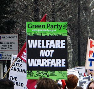 "Green Party of England and Wales - ""Welfare not Warfare"" sign, indicating the Green Party's policy towards social justice and non-violence"