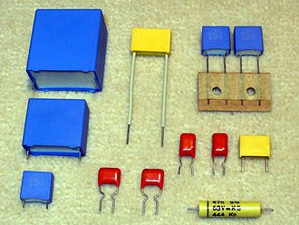 Film capacitor - Plastic film capacitors potted in rectangular casings, or dipped in epoxy lacquer coating (red color)