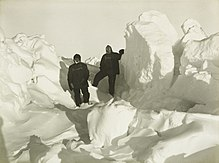 Two men in heavy clothing stand surrounded by mounds of ice which extend well above the height of their heads