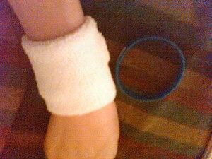 Wristband - A white terrycloth wristband on an arm, next to a blue silicone wristband.