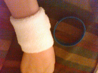 Wristband - A white terrycloth wristband on an arm, next to a blue silicone wristband.