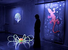 A person in silhouette stands gazing down at a piece of art on the floor. Paintings on the wall behind the person are glowing from the UV light.