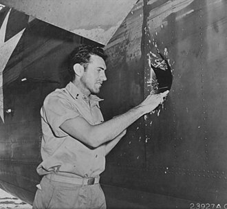 Louis Zamperini - Zamperini examines a hole in his B-24D Liberator Super Man made by a 20 mm shell over Nauru.