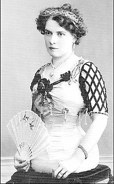 Antonia Matt um 1900: eine elegant gekleidete Dame mit eng geschnürter Taille und einem Fächer sitzt auf einem Kissen. Man sieht, dass sie keine Beine hat
