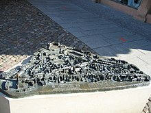 An oblique view from above of a relief model set up in downtown Wittenberg, which rests on an approximately waist-high base made of white stone.  The relief is made of bronze and has an approximately triangular plan.  It shows a model of buildings, streets, squares and groups of trees;  the houses are a few inches high.  On the front edge there are two text panels in raised normal script and in Braille, and some selected places and buildings are also labeled in this way.