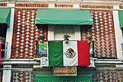 """Hausfassade in Puebla mit der Fahne verziert, für die """"Fiesta de la independencia""""."""