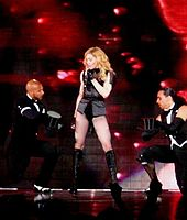 A blond woman standing on a stage, wearing a black coat over a black leotard and long black boots. She is flanked by two males in formal suits. The men are sitting on one leg and holds out their hats to the woman who sings into a microphone in her left hand. The backdrop displays tiny sparkling red lights.