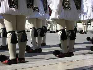Παράταξη ευζώνων: Διακρίνονται η φουστανέλα, οι ευζωνικές κάλτσες, οι καλτσοδέτες και τα τσαρούχια