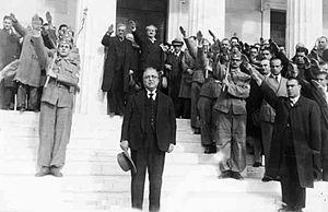 Ο Ι. Μεταξάς ασκεπής σε στάση προσοχής στίς σκάλες της Παλαιάς Βουλής πιθανώς σε ανάκρουση Εθνικού Ύμνου. Διακρίνονται ο Κ. Κοτζιάς και ο π. Υπουργός Τουρκοβασίλης με τους παρισταμένους να αποδίδουν τον φασιστικό χαιρετισμό.