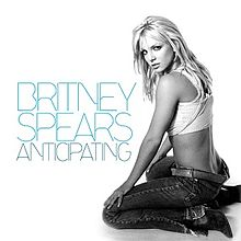 "Image of a blond woman. She sits on the right side of the image. She wears low-cut jeans, boots and a white top. She is looking over her shoulder into the camera. On the left, the words ""BRITNEY SPEARS ANTICIPATING"" are written in big blue capital letters."