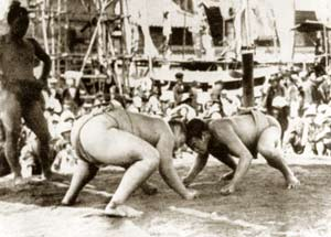 Two sumo wrestlers confront each other on a platform, their heads touching and their fists on the ground. To the side, a third man, also in a wrestling outfit, looks on; in the background, a crowd watches.