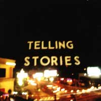 "A blurred photograph of a sign reading ""TELLING STORIES"""