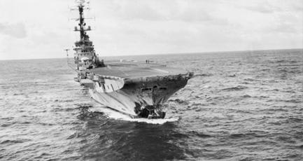 An aircraft carrier underway at sea. The bow of the aircraft carrier has been torn off, and the surrounding area is damaged and scorched.